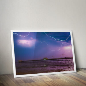 Photo of thunderstorm storm with 3 lightning strikes with a purple and blue hue.